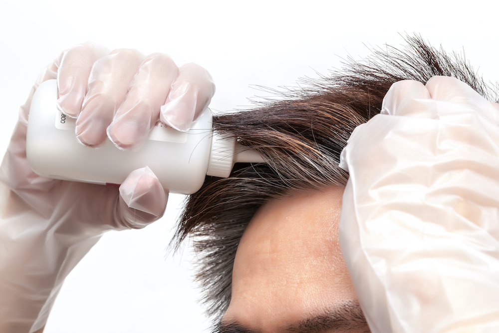 A man giving his grey hair a root touch up.