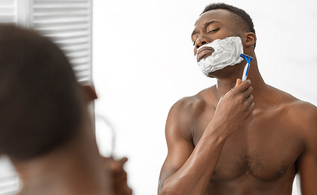 A man using aftershave as part of his skincare routine.