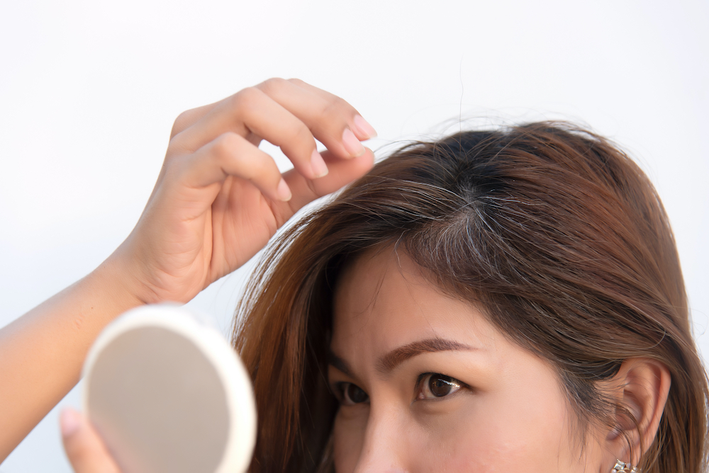 A woman seeing gray hair start to form.